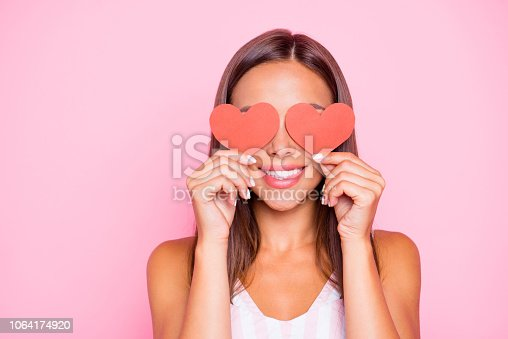 Close up portrait of cute sweet pretty beautiful lovely gorgeous hold two small little thematic red shape cards close eyes she isolated on vivid pink pastel background in her white casual wear