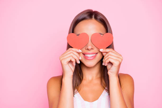 Close up portrait of cute sweet pretty beautiful lovely gorgeous hold two small little thematic red shape cards close eyes she isolated on vivid pink pastel background in her white casual wear stock photo