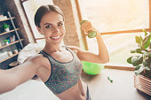 istock Close up portrait of delightful beautiful ideal slim sportive powerful muscular positive woman dressed in tight gray top demonstrating her biceps taking selfie having video call 932283612