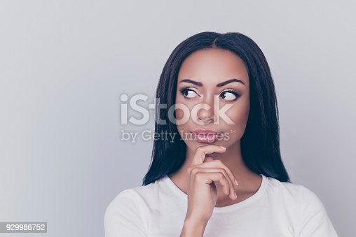 istock Close up portrait of dreamy afro looking away, touching chin with her arm, her thoughts are far away, wearing white casual outfit, isolated on gray background, has nice dark hair, light daily make up 929986752