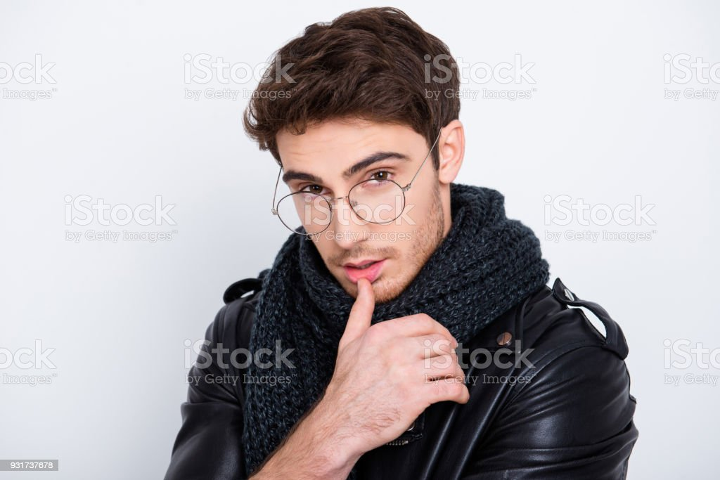 Close up portrait of dreamy, thoughtful, concentrated, attractive guy with scarf around neck holding finger on mouth, looking at camera isolated on grey background stock photo