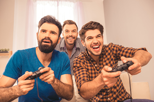 Close up portrait of excited happy cheerful men play video game