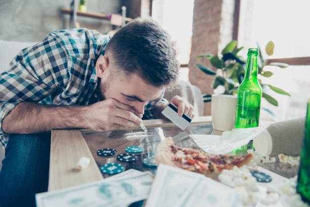 Close up portrait of exhausted drunk overdosed guy dressed in checkered shirt, he is sniffing a snorting line made of drugs on a table stock photo