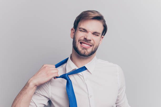 Close up portrait of exhausted frustrated stressed handsome sad unhappy upset entrepreneur trying to take off uncomfortable blue tie formal wear isolated on gray background copy-space Close up portrait of exhausted frustrated stressed handsome sad unhappy upset entrepreneur trying to take off uncomfortable blue tie formal wear isolated on gray background copy-space undressing stock pictures, royalty-free photos & images