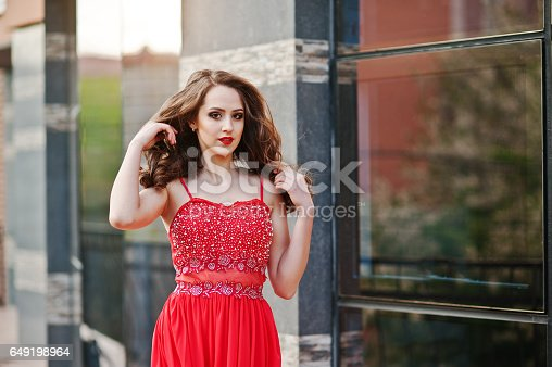 istock Close up portrait of fashionable girl at red evening dress posed background mirror window of modern building 649198964