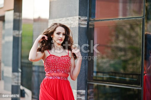 istock Close up portrait of fashionable girl at red evening dress posed background mirror window of modern building 649198976