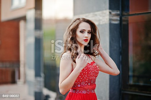 istock Close up portrait of fashionable girl at red evening dress posed background mirror window of modern building 649199032