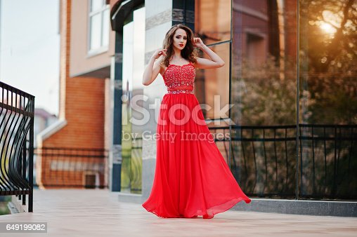 istock Close up portrait of fashionable girl at red evening dress posed background mirror window of modern building 649199082