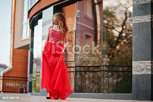 811572880 istock photo Close up portrait of fashionable girl at red evening dress posed background mirror window of modern building 649199128