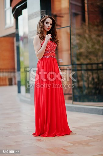 istock Close up portrait of fashionable girl at red evening dress posed background mirror window of modern building 649199144