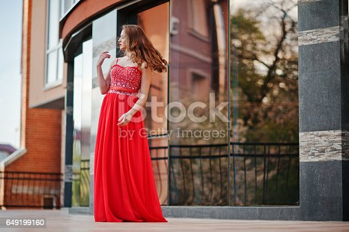 istock Close up portrait of fashionable girl at red evening dress posed background mirror window of modern building 649199160