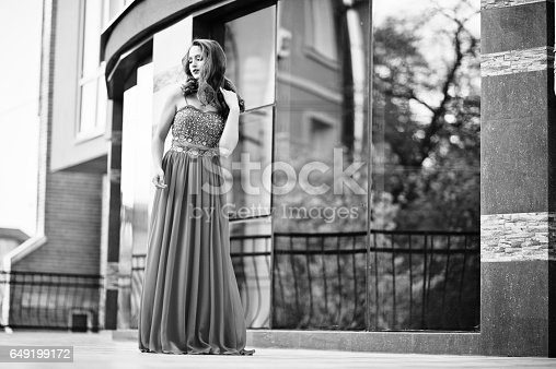 istock Close up portrait of fashionable girl at red evening dress posed background mirror window of modern building 649199172