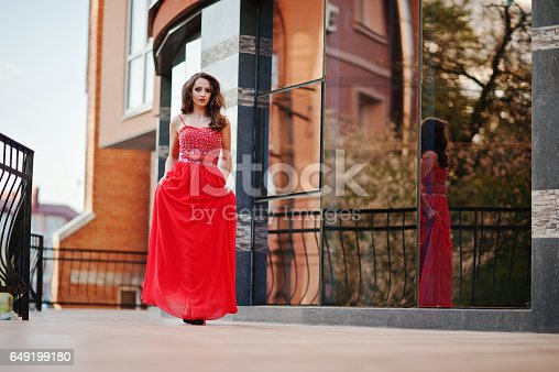 istock Close up portrait of fashionable girl at red evening dress posed background mirror window of modern building 649199180