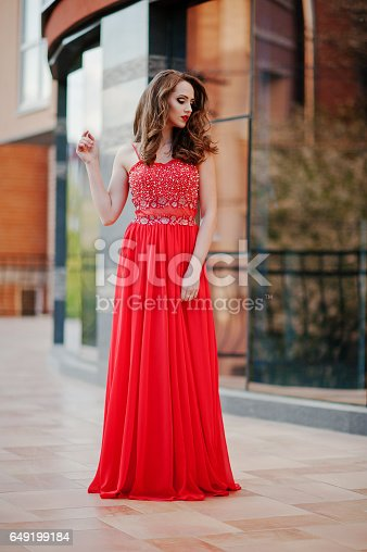 istock Close up portrait of fashionable girl at red evening dress posed background mirror window of modern building 649199184