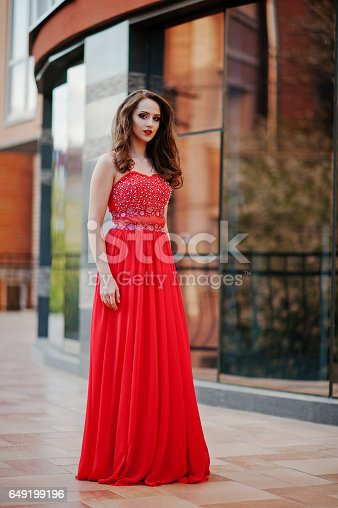 istock Close up portrait of fashionable girl at red evening dress posed background mirror window of modern building 649199196