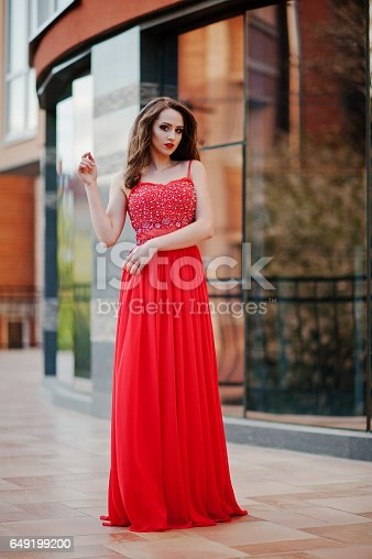 istock Close up portrait of fashionable girl at red evening dress posed background mirror window of modern building 649199200