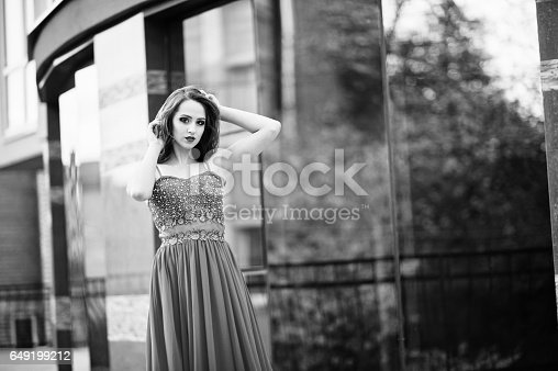 istock Close up portrait of fashionable girl at red evening dress posed background mirror window of modern building 649199212
