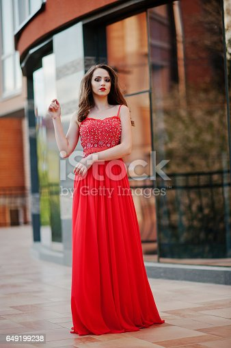 istock Close up portrait of fashionable girl at red evening dress posed background mirror window of modern building 649199238
