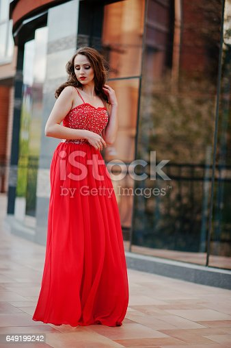 istock Close up portrait of fashionable girl at red evening dress posed background mirror window of modern building 649199242