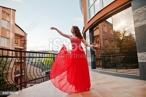 istock Close up portrait of fashionable girl at red evening dress posed background mirror window of modern building 649199248