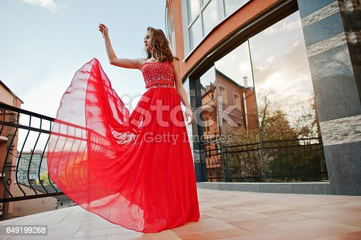 istock Close up portrait of fashionable girl at red evening dress posed background mirror window of modern building 649199268