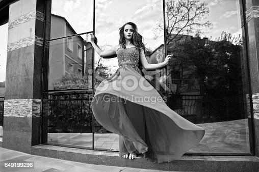 istock Close up portrait of fashionable girl at red evening dress posed background mirror window of modern building 649199296