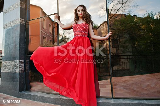 istock Close up portrait of fashionable girl at red evening dress posed background mirror window of modern building 649199298