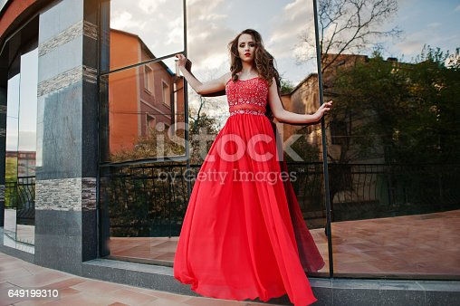 istock Close up portrait of fashionable girl at red evening dress posed background mirror window of modern building 649199310