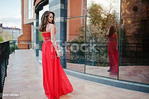 istock Close up portrait of fashionable girl at red evening dress posed background mirror window of modern building 649199394