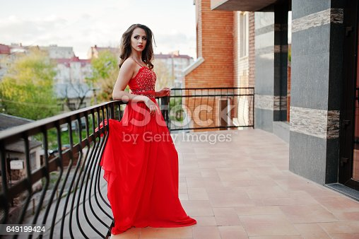 811572880 istock photo Close up portrait of fashionable girl at red evening dress posed background mirror window of modern building 649199424