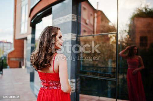 811572880 istock photo Close up portrait of fashionable girl at red evening dress posed background mirror window of modern building 649199428