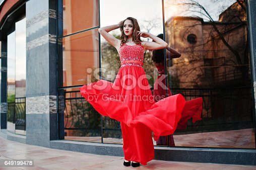 811572880 istock photo Close up portrait of fashionable girl at red evening dress posed background mirror window of modern building 649199478