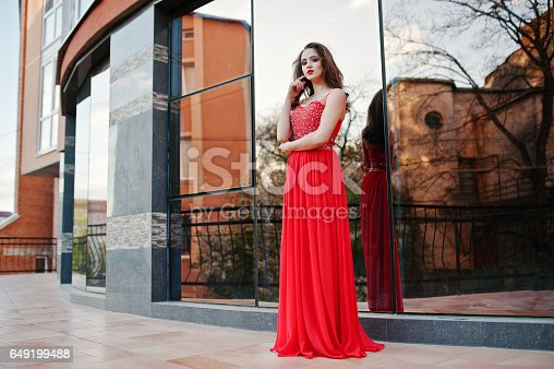 811572880 istock photo Close up portrait of fashionable girl at red evening dress posed background mirror window of modern building 649199488