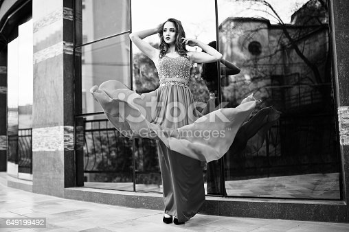 811572880 istock photo Close up portrait of fashionable girl at red evening dress posed background mirror window of modern building 649199492