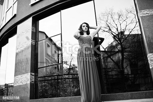 811572880 istock photo Close up portrait of fashionable girl at red evening dress posed background mirror window of modern building 649201158