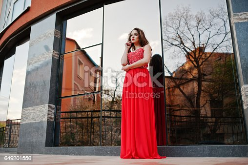 811572880 istock photo Close up portrait of fashionable girl at red evening dress posed background mirror window of modern building 649201556