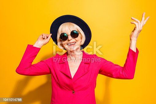 Close up portrait of fashioned and smiling granny hold han in the hands and looking at camera isolated on vivid yellow background