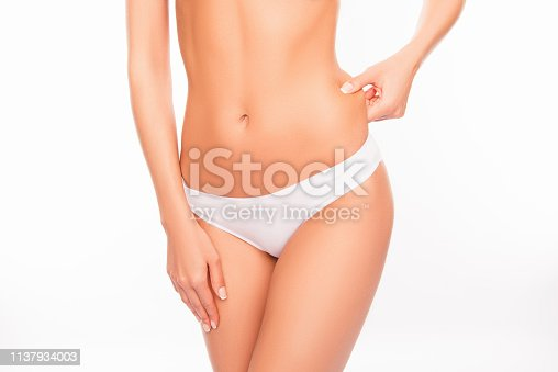 521792753istockphoto Close up portrait of fit woman checking fat on her side 1137934003