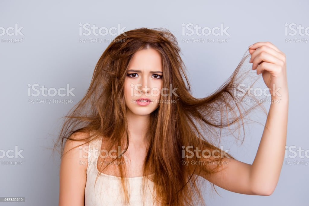 Close up portrait of frustrated young girl with messed hair on pure  background, wearing white casual singlet, holding her hair stock photo