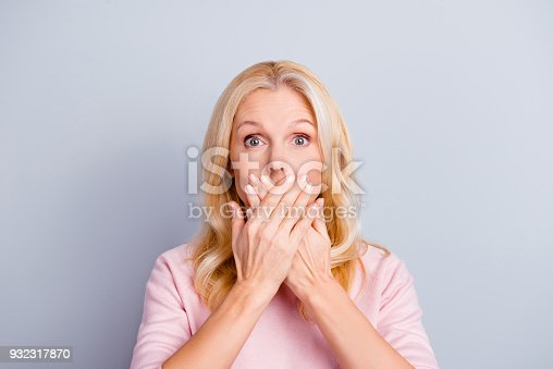 istock Close up portrait of funky curious cunning beautiful talkative gentle wondered astonished amazed lovely journalist grandmother grandma granny closes covers mouth isolated on gray background 932317870