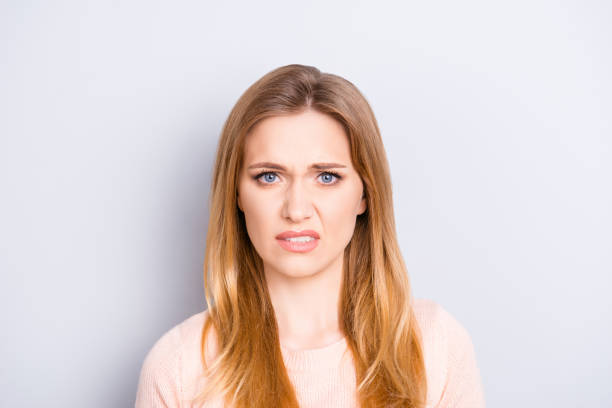Close up portrait of funny confused puzzled unhappy upset sad uncertain unsure beautiful pretty charming grimacing woman with long blonde hairdo isolated on gray background opy-space stock photo