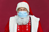istock Close up portrait of funny old bearded surprised Santa Claus wearing costume, glasses, face mask looking at camera standing on Christmas red background. Covid 19 coronavirus safety protection concept. 1280356964