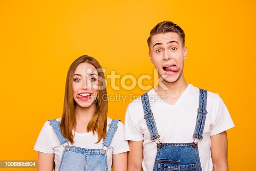 1092709104 istock photo Close up portrait of funny playful lovely adorable young cute couple showing tongues out, looking straight over yellow background, isolated 1006805804