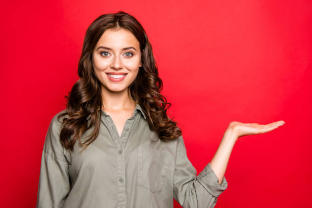 close up portrait of gorgeous, adorable, good-looking young woman with curly modern hairstyle in blouse hold invisible product on palm of hand isolated on vivid red background - dłoń zdjęcia i obrazy z banku zdjęć