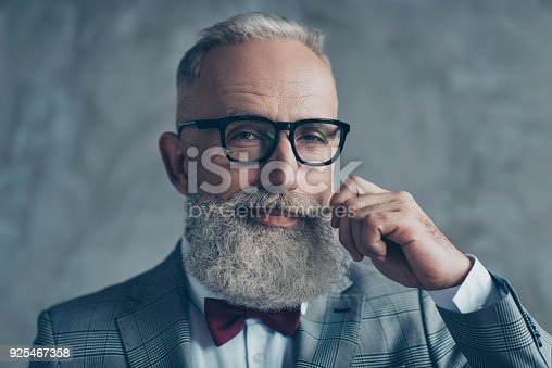 istock Close up portrait of grinning old-fashioned trendy elegant wealthy professional flirty trendsetter hipster grandpa sharp dressed with maroon bow-tie twisting white mustache isolated on grey background 925467358