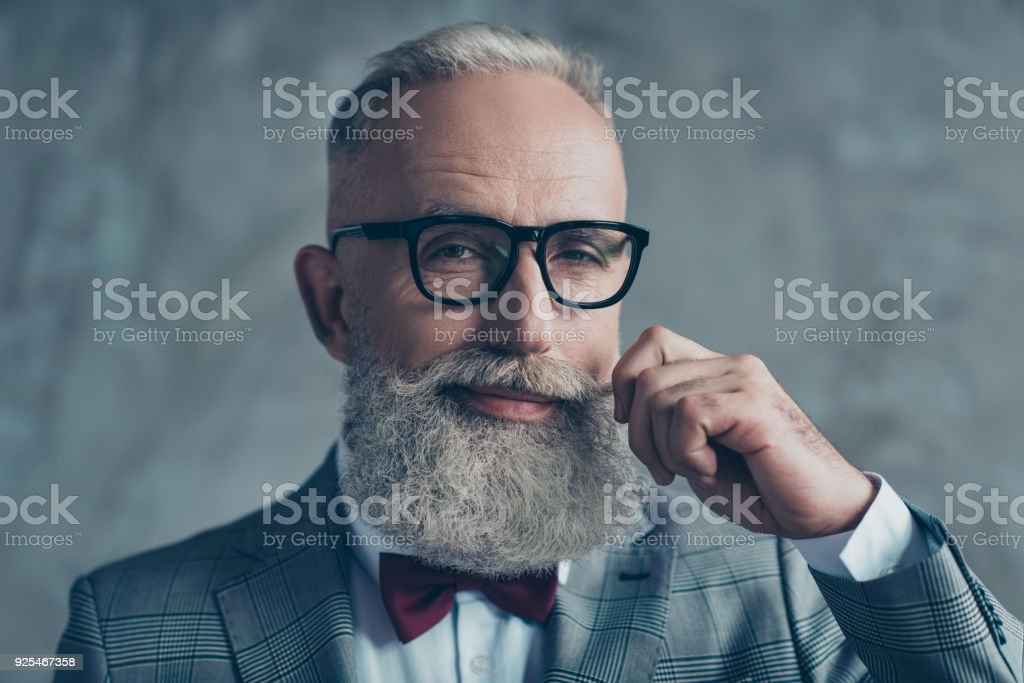 Close up portrait of grinning old-fashioned trendy elegant wealthy professional flirty trendsetter hipster grandpa sharp dressed with maroon bow-tie twisting white mustache isolated on grey background stock photo