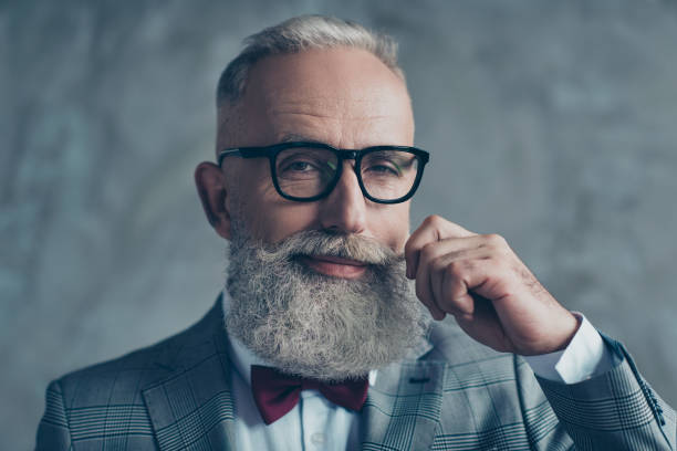 close up portrait of grinning old-fashioned trendy elegant wealthy professional flirty trendsetter hipster grandpa sharp dressed with maroon bow-tie twisting white mustache isolated on grey background - beard stock pictures, royalty-free photos & images