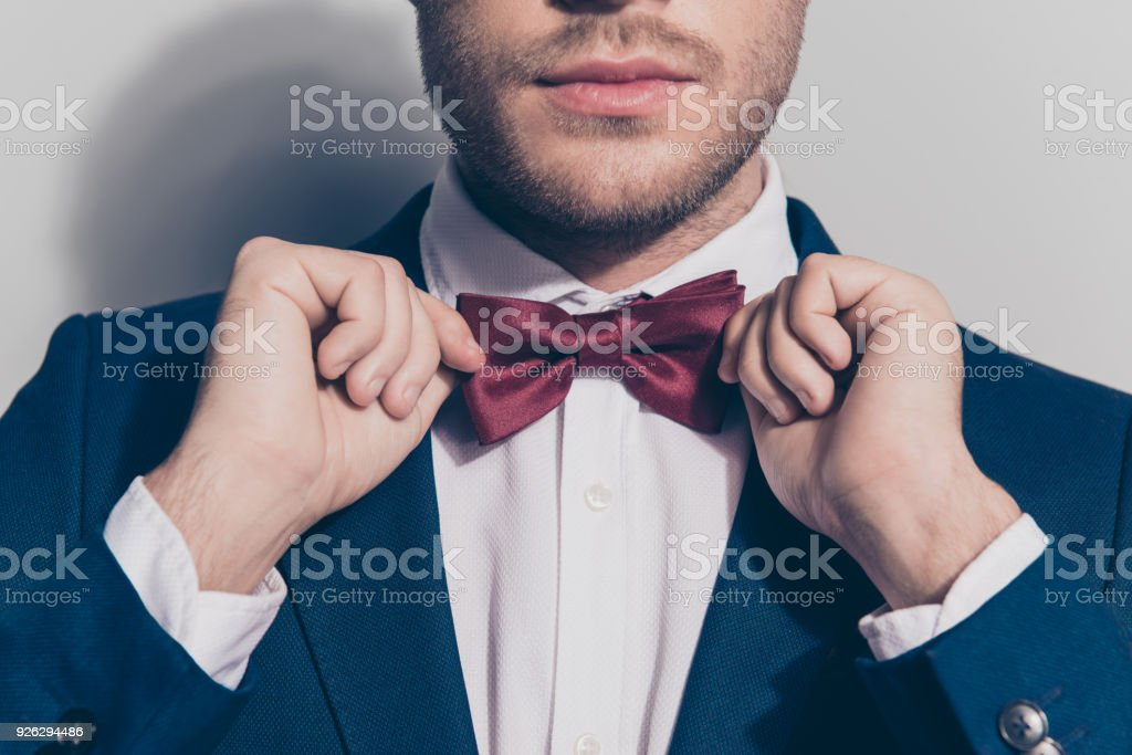 Close up portrait of half face - bearded stubble man ties a bowtie at the collar, correcting red bow on his white shirt over grey background stock photo