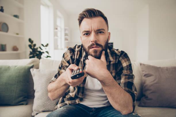 nahaufnahme portrait von schöne, attraktive, brünette mann schaut gespannt auf den fernseher für die geschehnisse auf dem bildschirm - dokumentation stock-fotos und bilder
