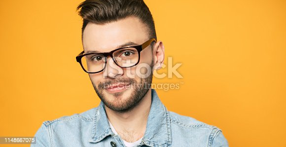 649754038 istock photo Close up portrait of handsome beard man in glasses isolated on yellow background 1148667075